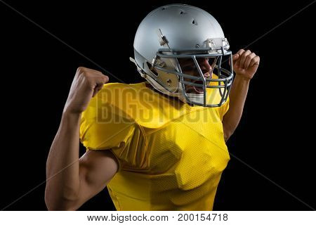 American football player flexing his muscles against a black background