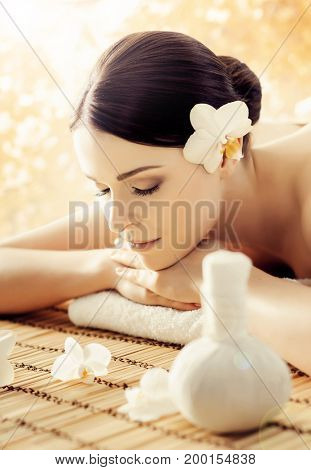 Massaging therapy over seasonal autumn background. Woman in spa.