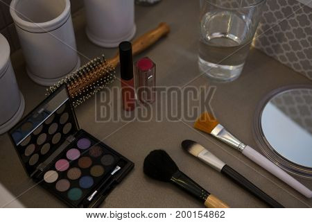 High angle view of beauty products with drinking glass on table