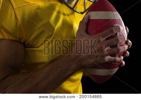 Mid section of American football player holding a ball with both his hands