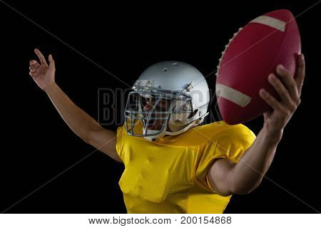 American football player cheering with ball in his hand against a black background