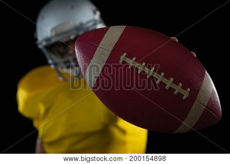 Close-up of American football player holding a ball in his hand