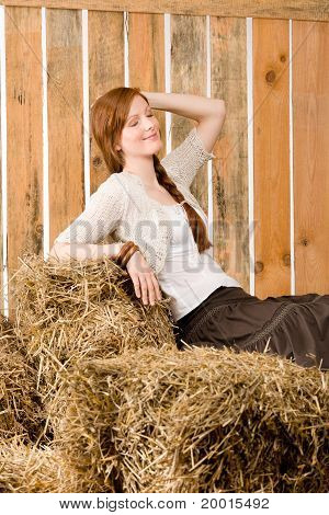 Romantic Young Woman Sitting On Hay Barn
