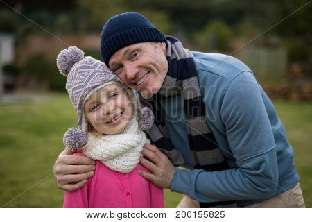 Portrait of smiling father and son standing together in the garden