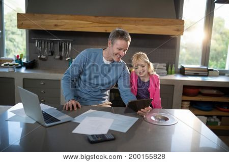 Father and daughter looking on a tablet in the kitchen