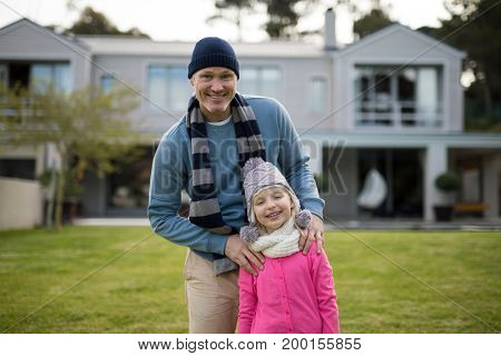 Portrait of smiling father and son standing in the garden