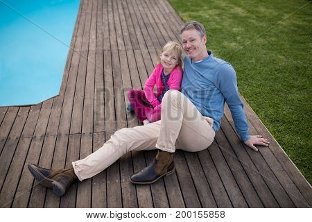 Smiling father and daughter sitting near the poolside