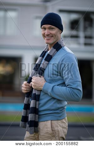 Portrait of smiling man in warm clothing standing outdoors