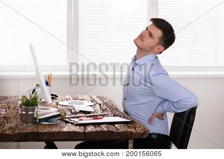Unhappy Young Businessman Suffering From Back Pain In Office