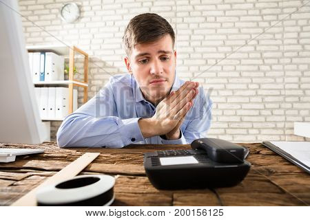 Portrait Of A Young Businessman Waiting For Call On Telephone On Wooden Desk