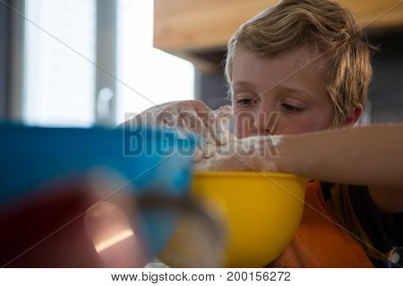 Boy preparing food in yellow container at kitchen counter