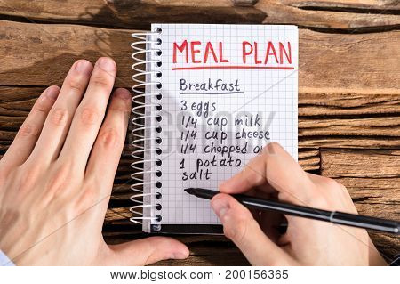 Close-up Of A Person's Hand Making Meal Plan On Notebook At Workplace