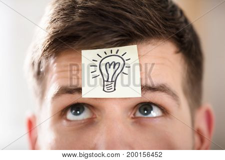 Close-up Of A Businessperson's Forehead With Electric Bulb Drawn On Sticky Note