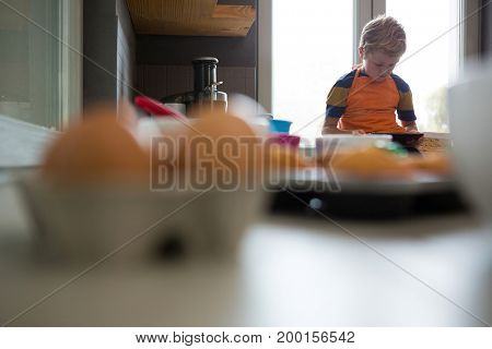 Boy using tablet while sitting at kitchen counter