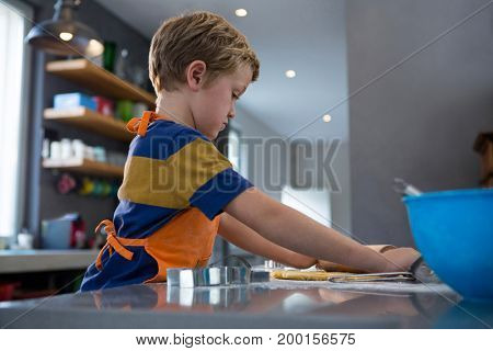 Side view of boy rolling dough in kitchen at home