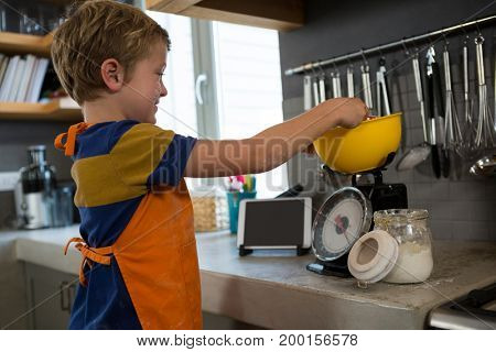 Boy measuring food in yellow bowl over kitchen scale at counter