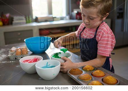 Boy mixing green batter at kitchen counter