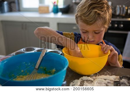 Boy preparing food in yellow bowl at kitchen counter