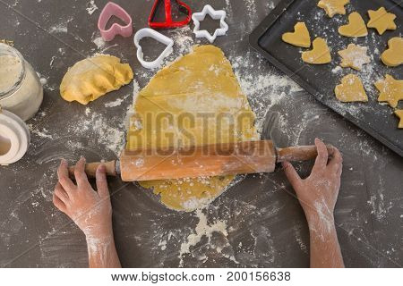 Cropped hands of boy preparing cookies at kitchen counter