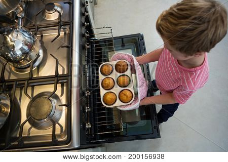 High angle view of boy holding muffin tin by oven in kitchen