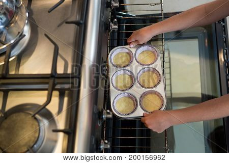 Cropped hands of boy holding muffin tin by oven in kitchen