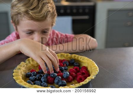 Boy preparing tart with berries in kitchen at home