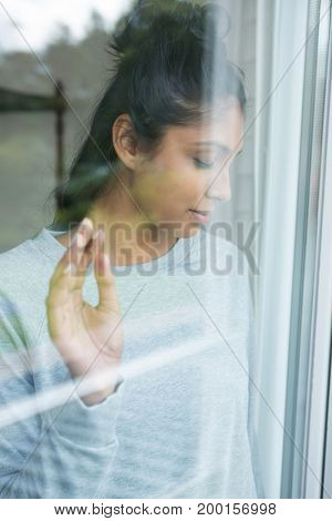 Young woman with eyes closed seen through glass window
