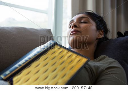Young woman with book sleeping on sofa at home