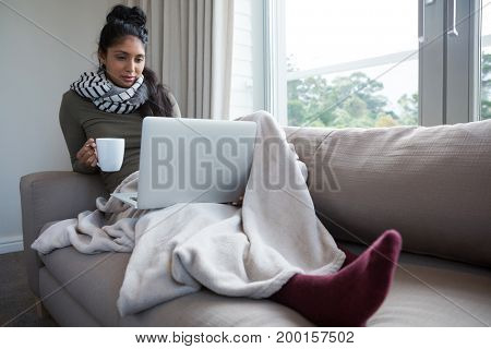 Full length of woman with coffee cup looking into laptop on sofa at home