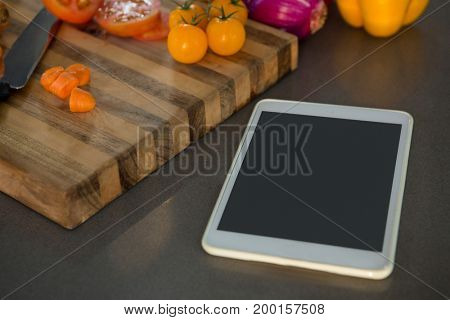 Digital tablet by vegetables on kitchen counter