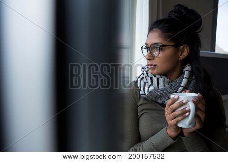 Young woman holding coffee cup by window at home
