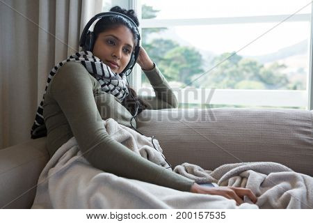 Relaxed young woman listening to music on sofa at home