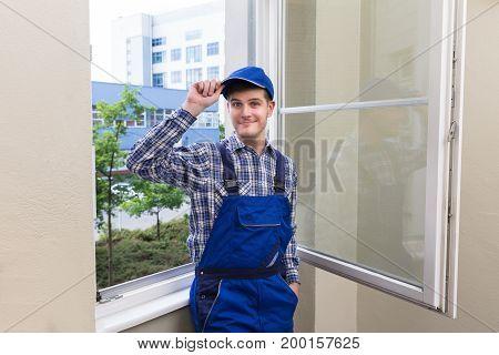 Portrait Of A Smiling Male Handyman Standing Near Glass Window