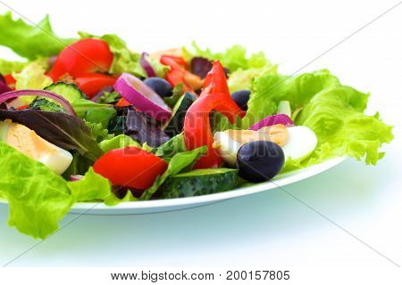 salad from fresh vegetables in a plate on a table, selective focus.
