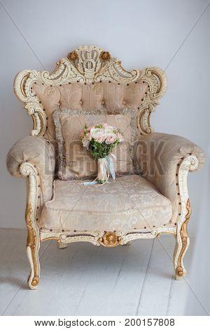 Elegant wedding flower bridal bouqet on texture armchair background