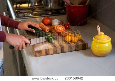 Cropped hands of woman cutting zucchini at kitchen counter