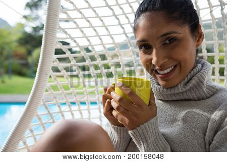 Portrait of smiling woman with coffee cup resting in swing chair at poolside