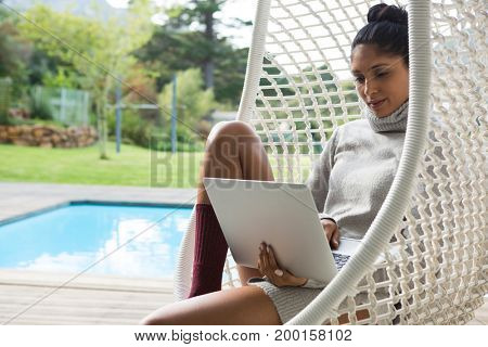 Young woman using laptop while resting on swing at poolside