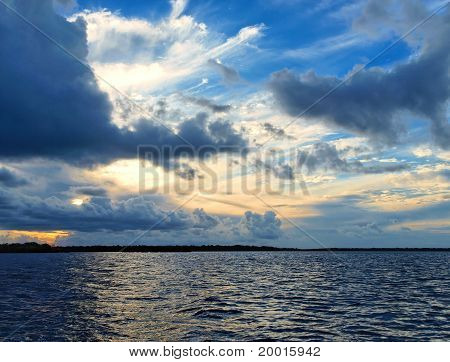 Multi Colored Clouds At Sunset Over Water