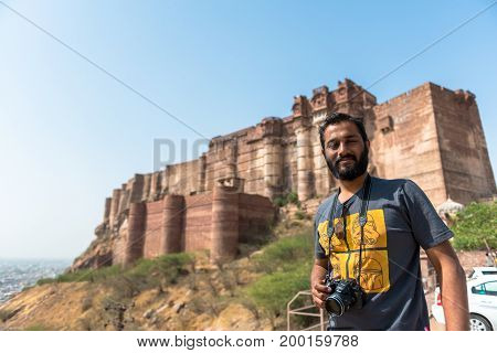 JODHPUR RAJASTHAN INDIA - MARCH 05 2016: Horizontal picture of indian tourist posing with his camera in front of Mehrangarh Fort in Jodhpur the blue city of Rajasthan in India.