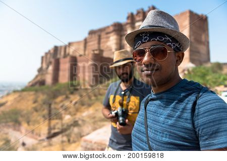 JODHPUR RAJASTHAN INDIA - MARCH 05, 2016: Close up picture of two indian tourists posing in front of Mehrangarh Fort in Jodhpur the blue city of Rajasthan in India.