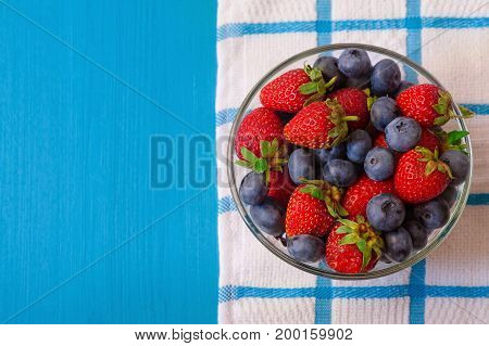 mixed berries in a a transparent cup on brown wooden background