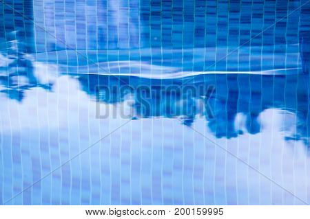 Blurred mosaic of the swimming pool in shades of blue.