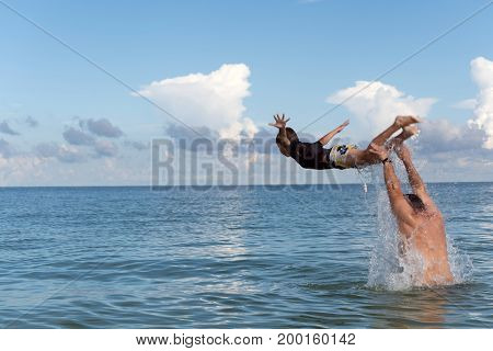 Dad throws his son out of the water playing with him on the beach, Florida, USA