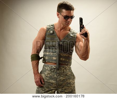 The tough army man holds up his gun.