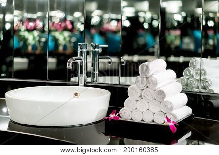 Interior of bathroom with washbasin faucet and white towel in hotel. Modern design of bathroom.