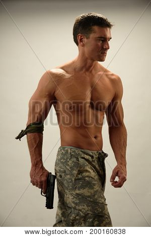 The hot army man stands looking buff.