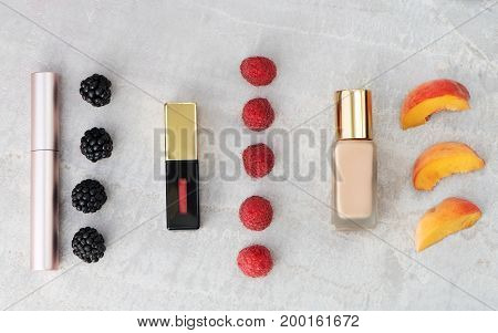 Beauty products everyday makeup with berries and peach for color comparison with copy space