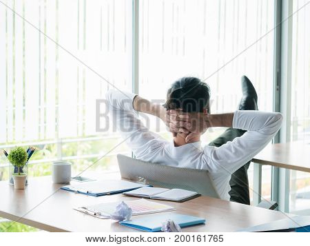 Businessman relaxing concept: businessman sitting with feet up at office desk looking out of window in break time