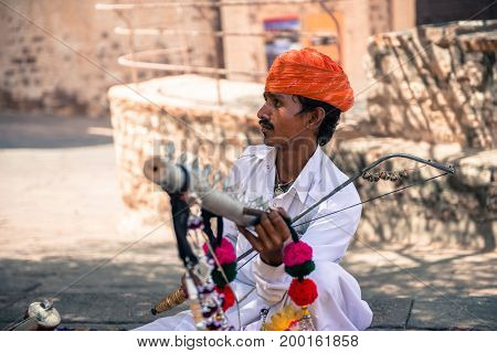 JODHPUR RAJASTHAN INDIA - MARCH 05 2016: Wide angle picture of local indian with mustache playing music inside Mehrangarh Fort in Jodhpur the blue city of Rajasthan in India.